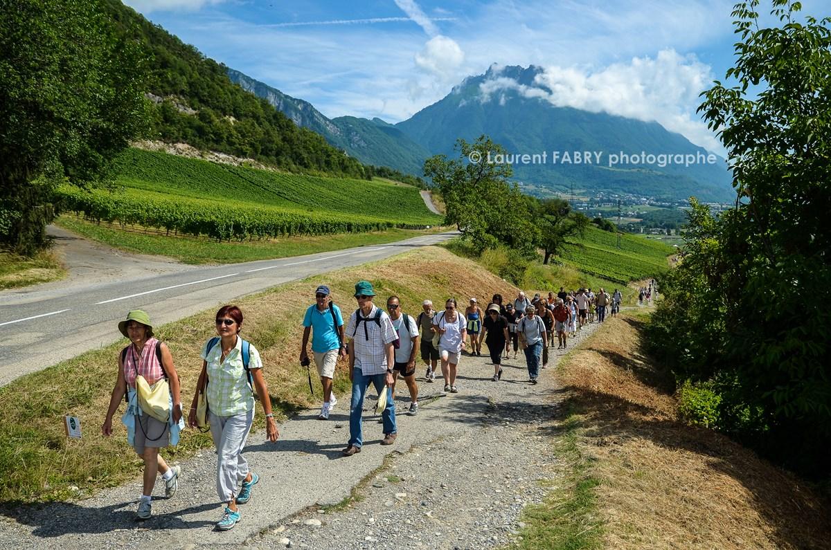 photographe tourisme sur une balade gourmande en Combe de Savoie : les participants s'éloignent de leur point de départ à Saint-Jean de la porte, devant la dent d'Arclusaz