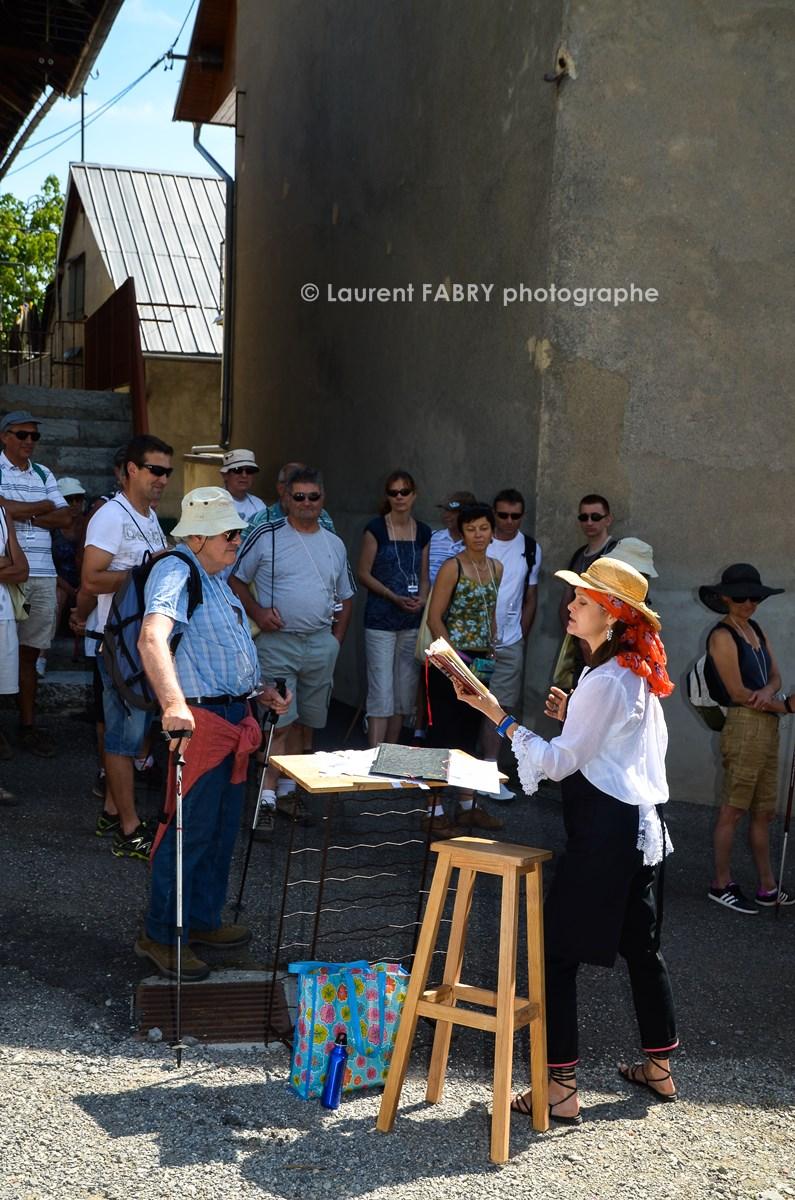 photographe tourisme sur une balade gourmande : une conteuse lit un texte aux participants de la balade gourmande en Combe de Savoie au hameau de la Baraterie, à Cruet, Savoie