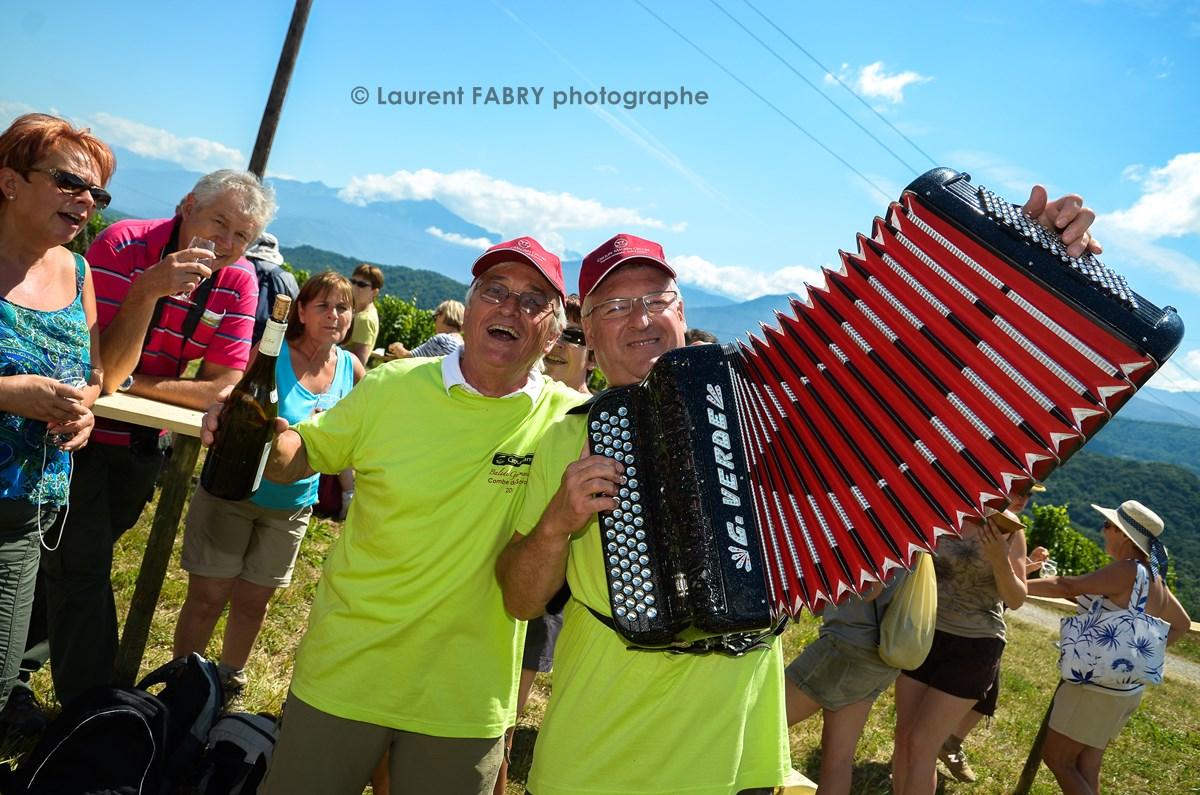 des bénévoles de la balade gourmande en Savoie animent une dégustation en musique (accordéon) et en chanson