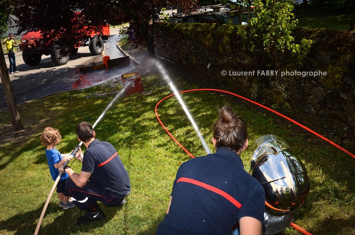 Photographe événementiel Pour Un Centre De Secours En Savoie : Les Apeurs Pompiers Montrent Aux Enfants Comment Tenir La Lance à Incendie