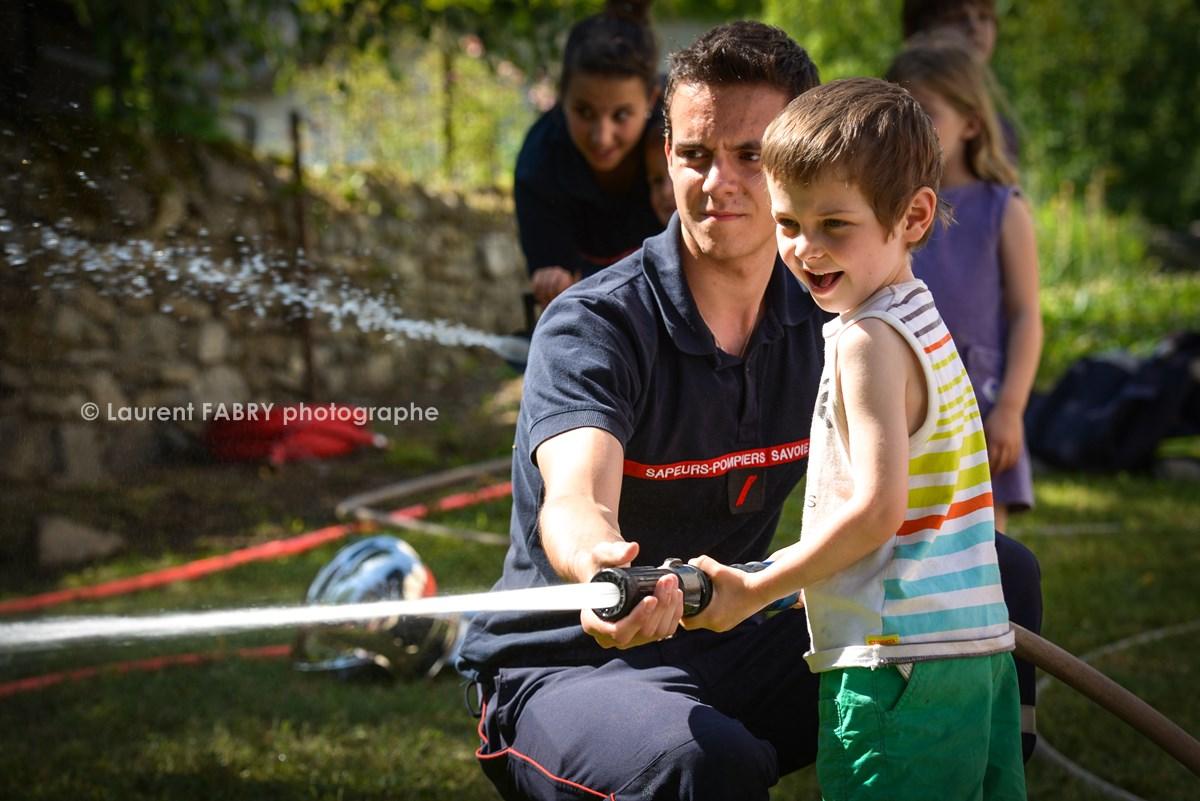 Photographe événementiel Pour Un Centre De Secours En Savoie : Les Enfants Découvrent Le Maniement De La Lance à Incendie