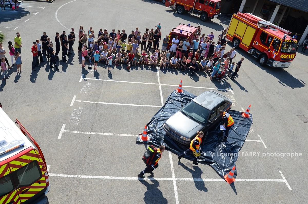 Photographe événementiel Pour Un Centre De Secours En Savoie : Les Pompiers Se Dirigent Vers Le Véhicule Accidenté Lors De La Manoeuvre De Secours Routier