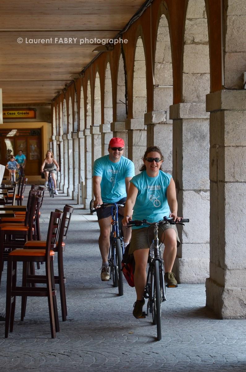 Photographe Urbanisme à Chambéry : Des Cyclistes Passent Sous Les Colonnes Du Carré Curial à Chambéry