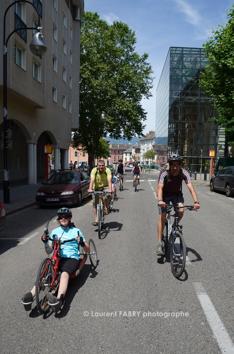 Photographe Urbanisme à Chambéry : Des Cyclistes Dont L'un D'entre Eux Sur Un Vélo Couché, Circulent Dans La Rue Devant Le Manège