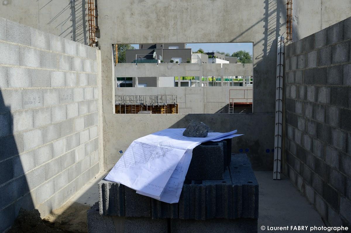 Photographe De Chantier à Aix-les-bains : Dans Une Des Futures Pièces Du Bâtiment, Un Plan Est Posé Sur Un Empilement De Parpaings