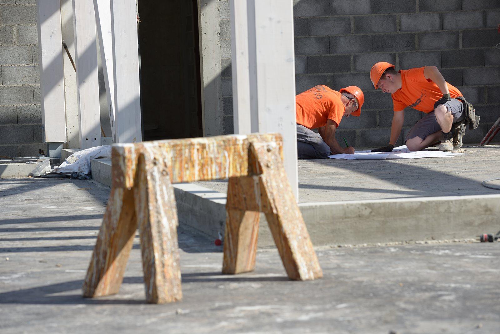 photographe de chantier à Aix-les-bains : des ouvriers consultent un plan posé au sol