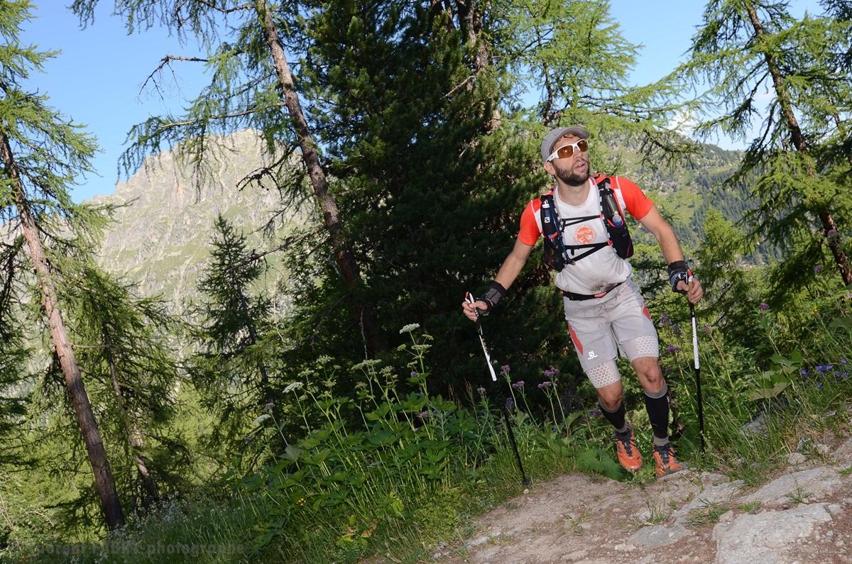 Photographe De Trail Running En Suisse : Un Coureur Débouche Sur Un Chemin Depuis Un Sentier