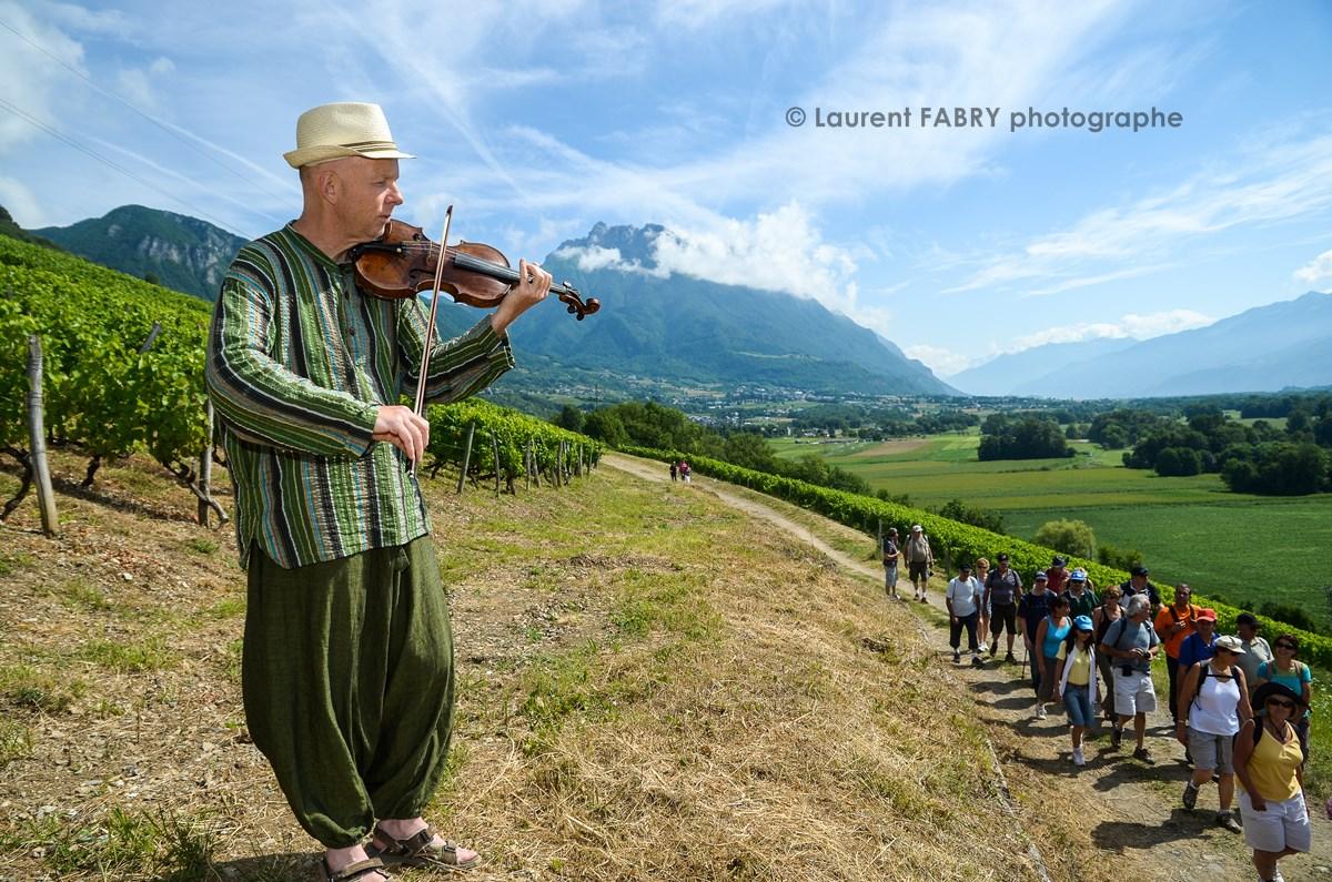 photographe tourisme sur une balade gourmande : un musicien violoniste accueille les promeneurs lors de la balade gourmande en Combe de Savoie, avec en arrière-plan la dent d'Arclusaz