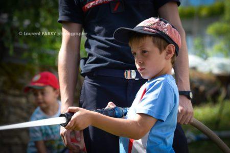 Photographe événementiel Pour Un Centre De Secours En Savoie : Un Jeune Garçon Tient Fièrement La Lance à Incendie