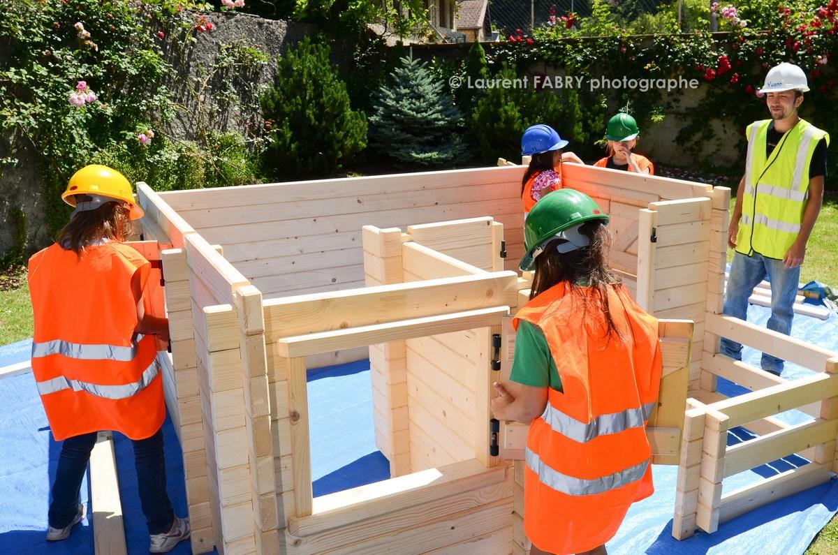Photographe tourisme en Tarentaise : des enfants construisent un chalet sur le village enfants (kid eco construction)