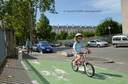Photographe Urbanisme à Chambéry : Une Petite Fille Portant Le Casque Et Les Lunettes De Soleil Roule Sur Une Piste Cyclable Près De La Gare De Chambéry