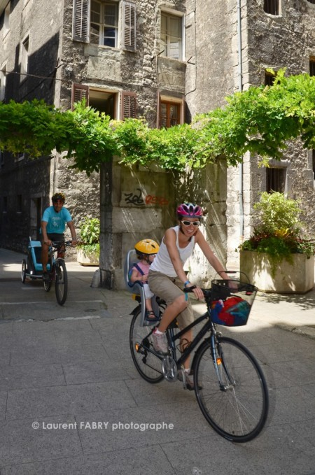 Photographe Urbanisme à Chambéry : Une Famille à Vélo Portant Leurs Enfants à L'arrière Circule Dans Les Traboules De Chambéry
