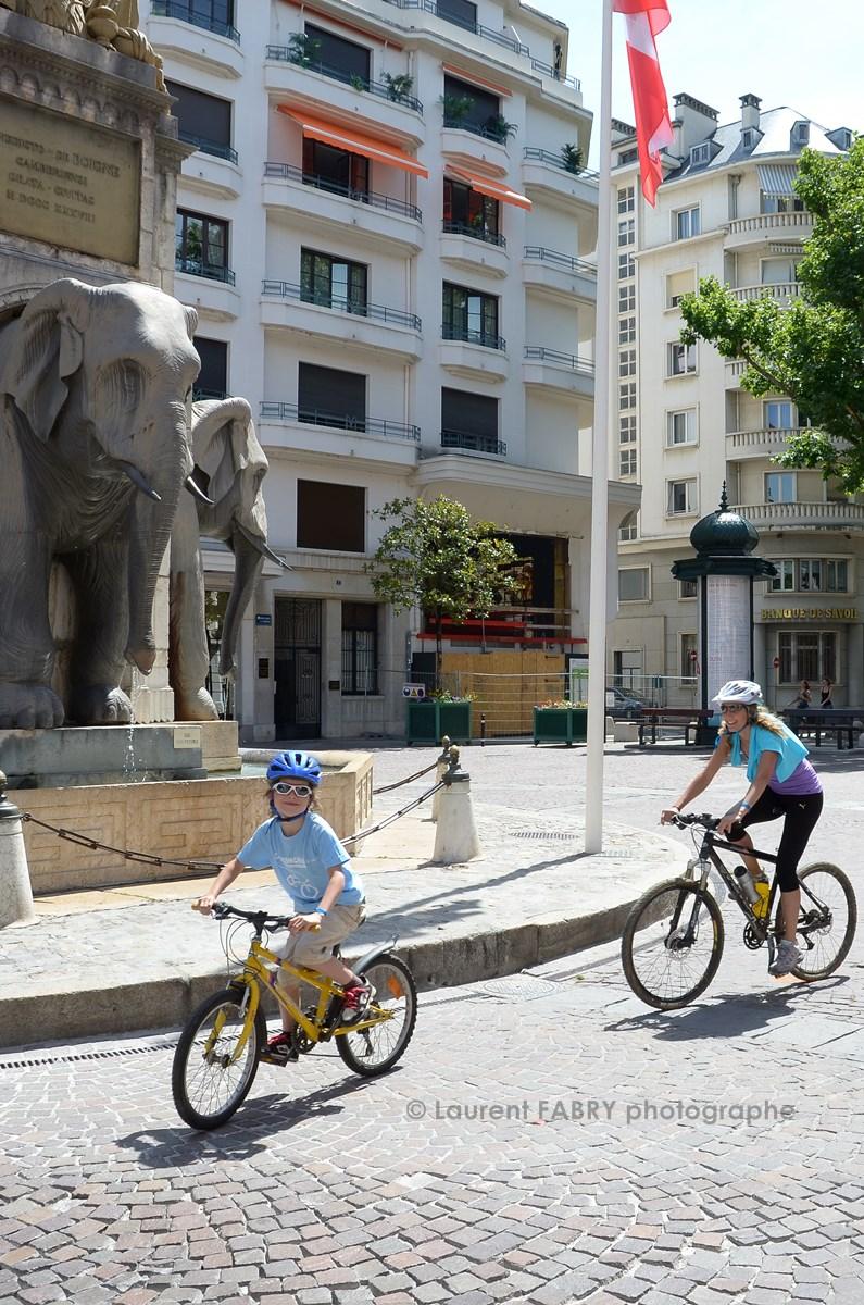 Photographe urbanisme à Chambéry : des enfants passent devant la fontaine des éléphants à Chambéry lors de la sortie vélo