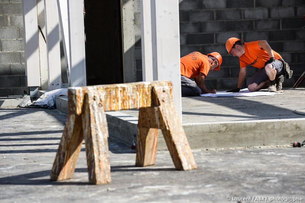 Photographe De Chantier à Aix-les-bains : Deux Ouvriers Consultent Un Plan Posé Sur Le Sol