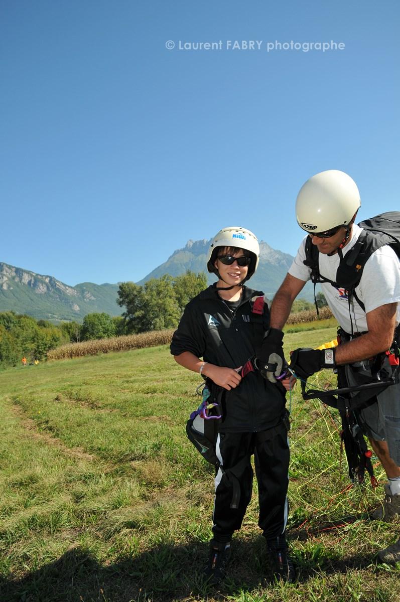 Photographe De Parapente En Combe De Savoie : Un Parapentiste Pilote Biplaceur Déséquipe Le Jeune Garçon Qu'il Vient De Faire Voler
