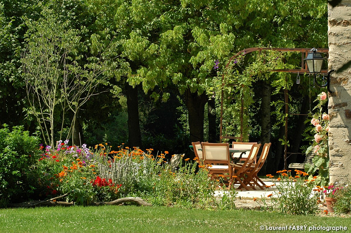 La Terrasse Et Son Salon De Jardin, Sous Une Cliématite Suspendue