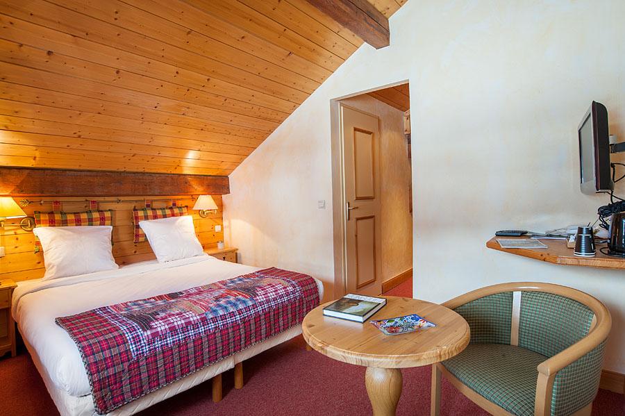 Photographe d'hôtel en Beaufortain : une chambre photographiée face au lit et porte de salle de bain