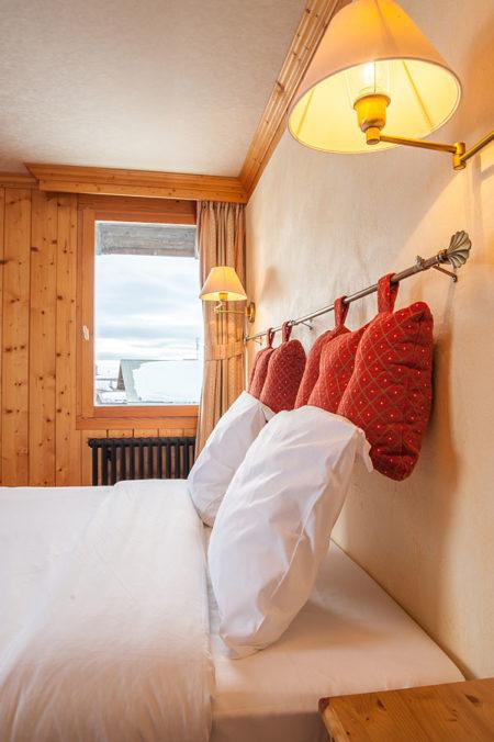 Photographe D'hôtel En Beaufortain : Une Chambre Photographiée Depuis Le Chevet Avec Vue Sur La Fenêtre