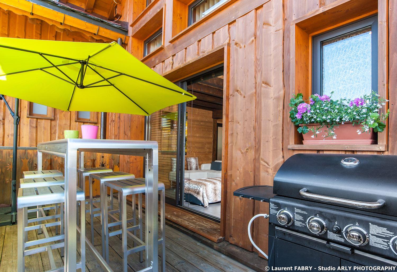 Shooting photo immobilier dans les Alpes : la terrasse du chalet et son barbecue