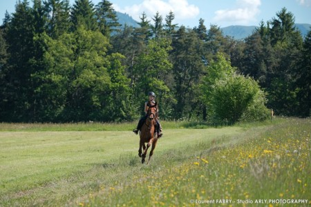 Une Cavalière Au Galop Dans Un Champs De Fleurs Lors Du Raid Multi-sports En Haute Savoie